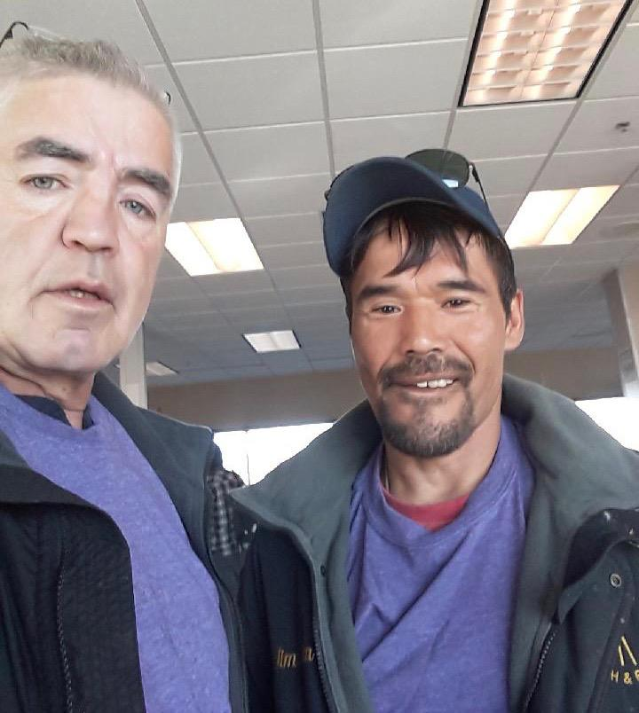 Bethel Search and Rescue members Sam Samuelson (left) and Jim Pete Jr. (right) get ready to board their flight to Kotzebue in the Anchorage airport. Both members are wearing purple shirts. The color is Ashley Johnson-Barr's favorite and has become a symbo