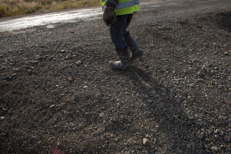 City Council Member Walter Nelson works with a road crew to reinforce Napakiak's gravel road system on September 27, 2018. The project will stabilize the roads and allow for safe transport of buildings away from the eroding riverbank in Napakiak, Alaska.