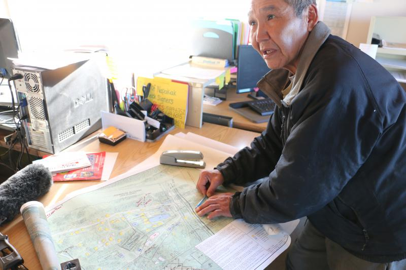 Napakiak City Council Member Walter Nelson shows where year by year, more of Napakiak's land has been washed away by the Kuskokwim River. The river eroded 82 feet of land between May 30, 2018 and September 7, 2018. Picture taken December 3, 2018.
