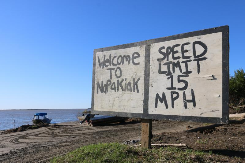 A sign on Napakiak's boat landing welcomes people to the community. Napakiak Mayor Joann Slats says that the sign is constantly moved back as the riverbank erodes. September 8, 2018.