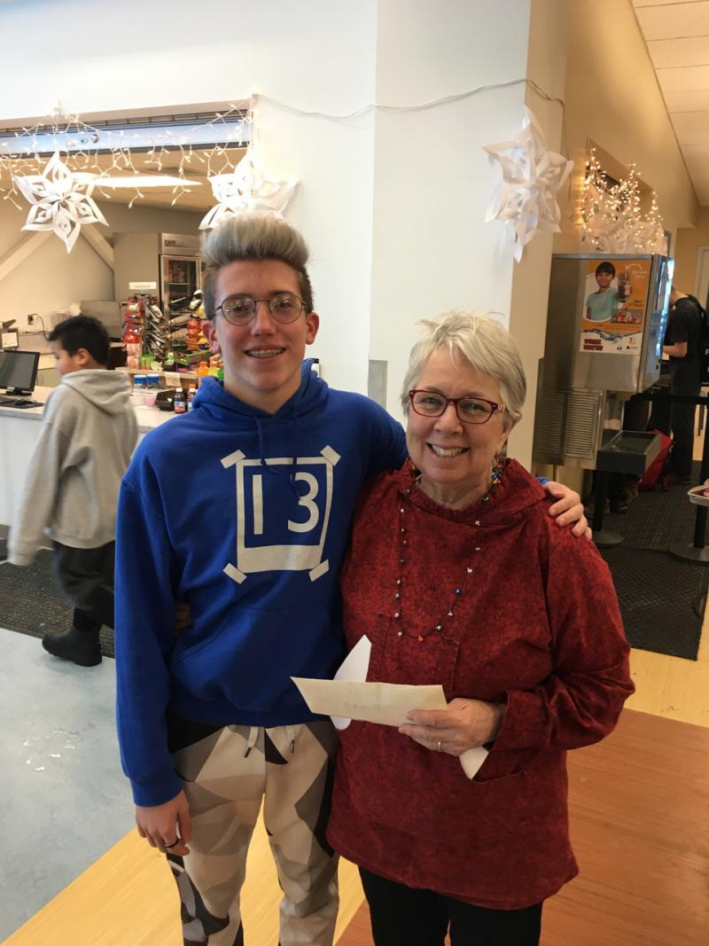 Dillon Crace of the Bethel Warrior Swim Team presents Bev Hoffman with a $50 donation to the YK Delta Lifesavers at the Cookie Extravaganza on Dec. 16, 2018.