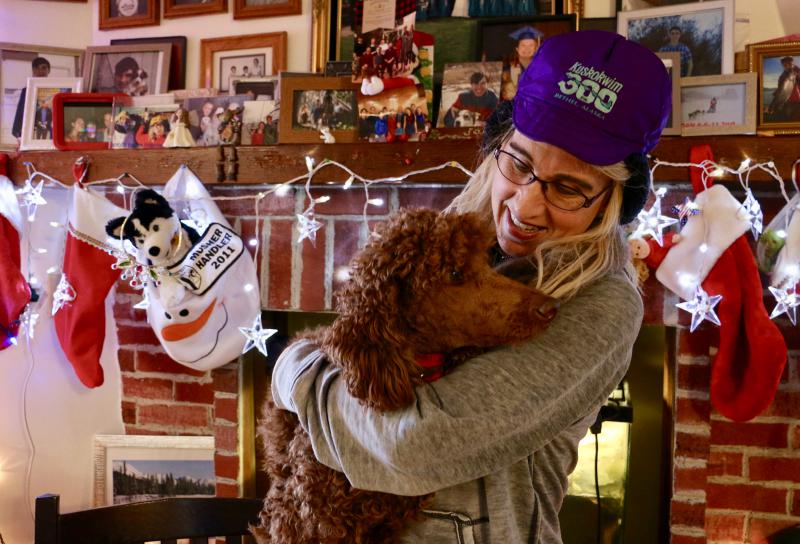 Jackie Klejka wears her signature K300 hat while holding her indoor dog Jersey inside her Bethel home, which is heavily decorated with sled dog paraphernalia. Klejka has been coordinating the K300 veterinary program since 1993.