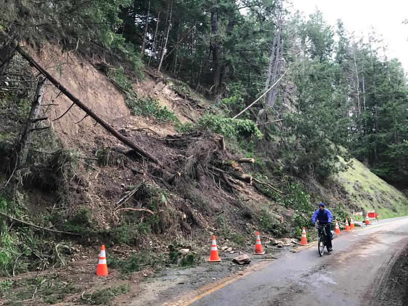 A bicyclist rides past a landslide blocking one lane of Philo-Greenwood Road just east of Elk.