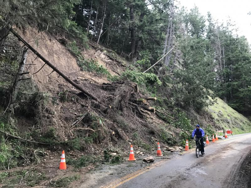 A bicyclist rides past a landslide blocking one lane of Philo-Greenwood Road just east of Elk in February 2017