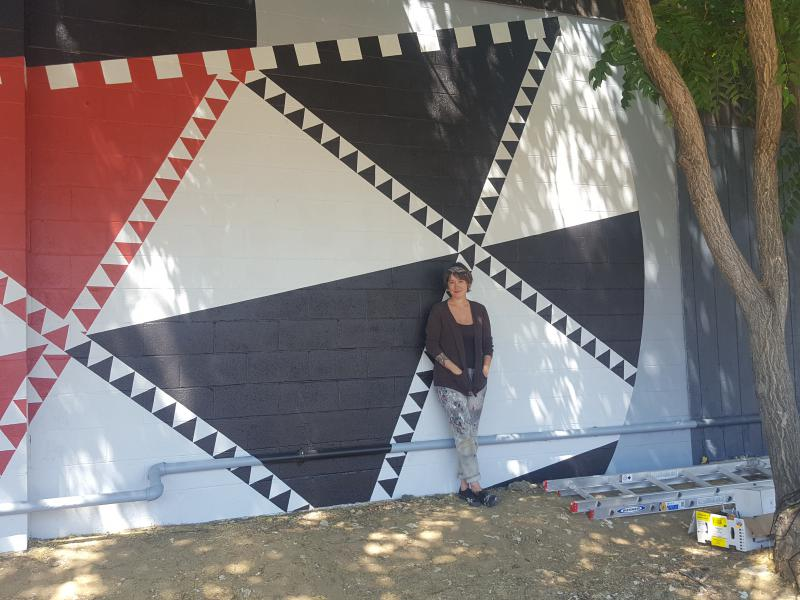 Artist Solane Roberdeau in front of her newly finished mural.