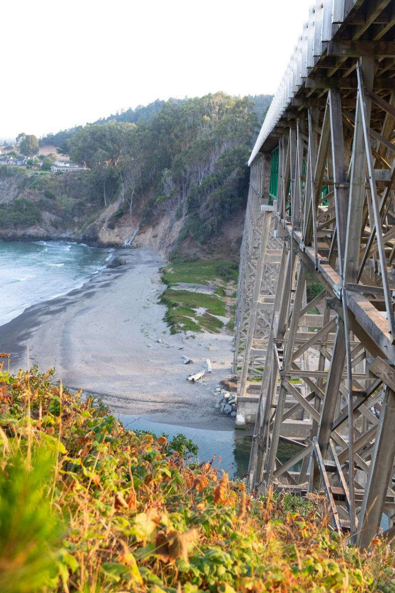 The historic Albion River Bridge. The area in the foreground and the eucalyptus-covered bluff in the distance are two sites where Caltrans plans grading and drilling operations.