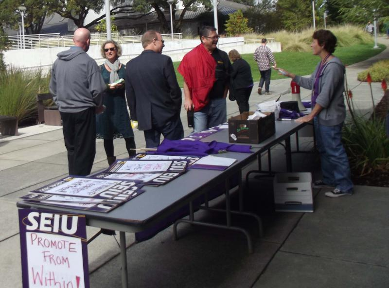 Toni Fort, chapter president of the local union representing temporary and classified staff at Mendocino College, stands behind a table speaking to people after a Unity Rally on campus Thursday.