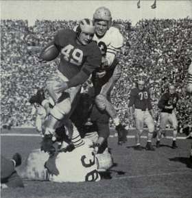 The University of Michigan's Bob Chappuis hurdling a tackler.