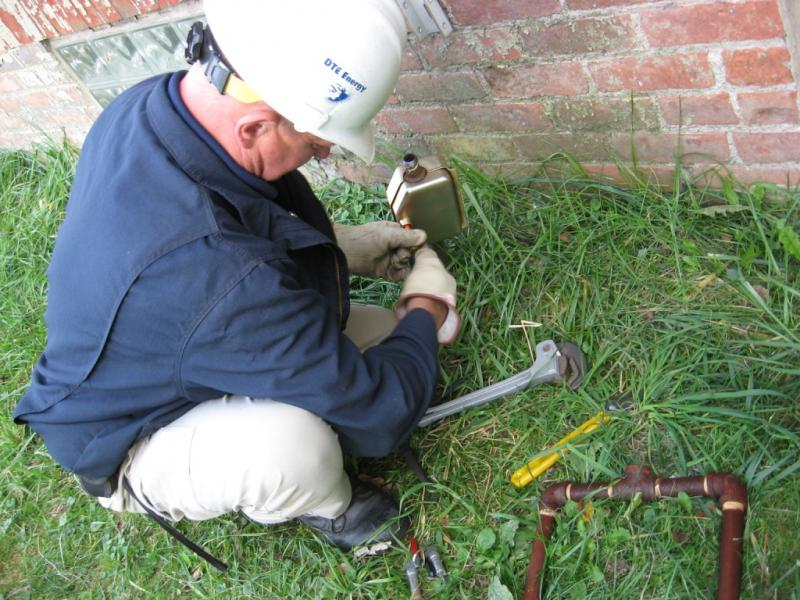DTE Energy theft investigator Keith Gross prepares a lock box to prevent thieves from tampering with a gas meter.