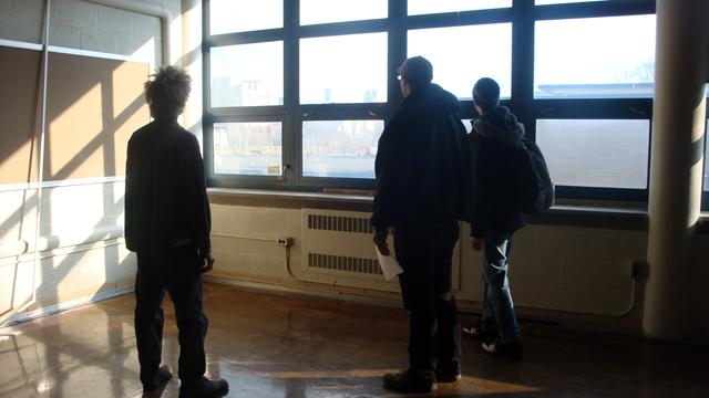 Joel Landy (left) shows Ben Christenson and a band mate around the former Malcolm X Academy building in Detroit.  Landy is turning the space into a music venue, with rehearsal space.
