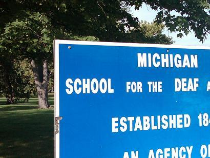 A sign stands at the entrance to the Michigan School for the Deaf in Flint
