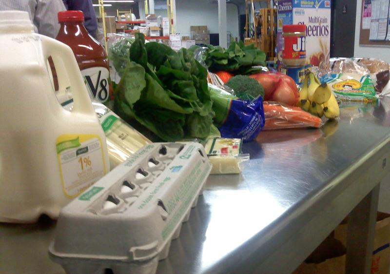 Groceries, including milk, eggs and produce, sitting on a counter.