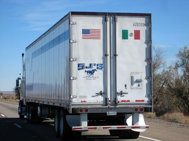 A tractor trailer with the U.S. and Mexican flags