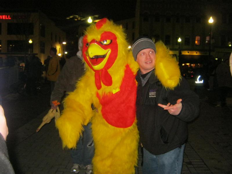 "A chicken dances and takes pictures with hundreds of ""chicken chuckers""."