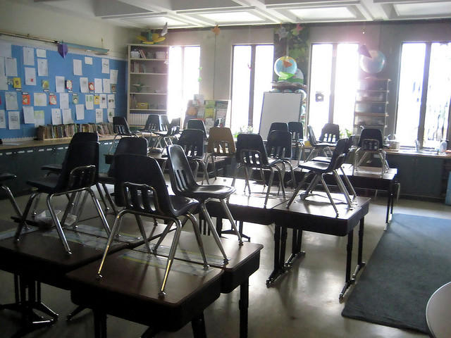An empty classrom with light shinging in from the windows.