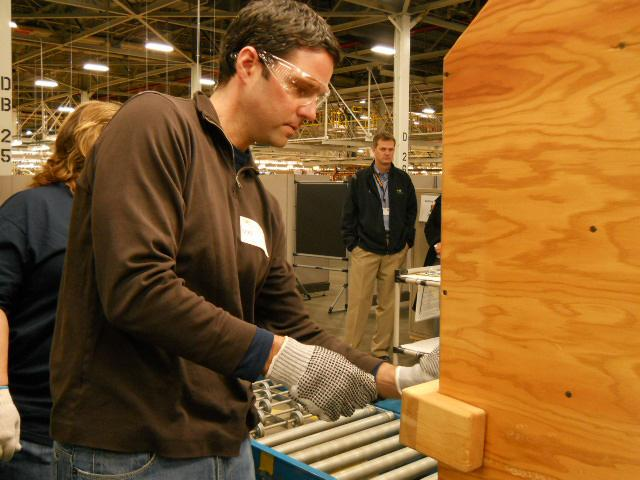 A team of reporters worked on each wooden car as they came down the assembly line.