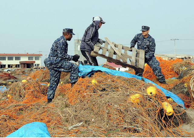 Members of the U.S. Navy help a Japanese man remove debris from the Misawa Fishing Port.
