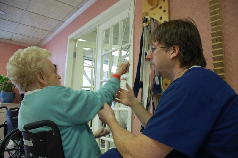 Second year occupational therapy student, Craig Morea, helps patient Shirley Teffner with her shoulder.