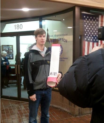 Kevin Karlinski, student from Western Michigan University, outside Congressman Upton's district office to deliver oversized asthma inhaler. Behind him, more community members drop off inhalers in Congressman Upton's office.