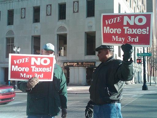 Millage increase opponents stand outside Lansing city hall