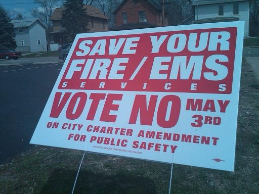 Red-and-white signs can be found all across Jackson these days. The signs, which look very similar, carry very different messages: Some encourage city residents to vote for merging Jackson's police and fire departments, while others oppose it.