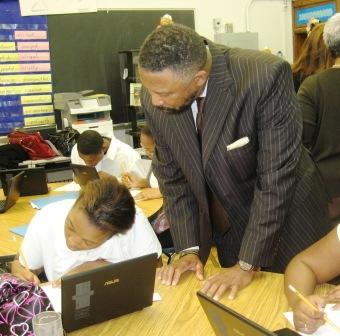 Detroit Public Schools Emergency Financial Manager Robert Bobb watches Denby High School student Erica Green use a new netbook in geometry class.
