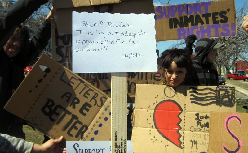 Post-card-sized protest sign aims to demonstrate limitations.