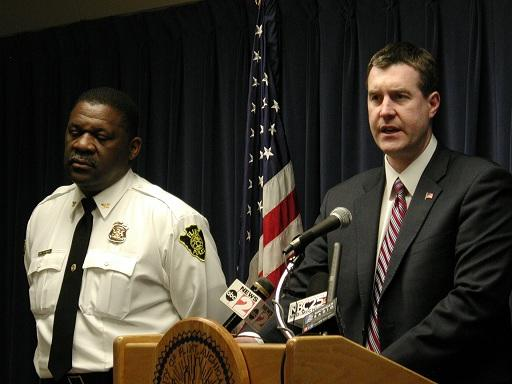 Flint mayor Dayne Walling (right) at a news conference, flanked by public safety chief Alvern Lock
