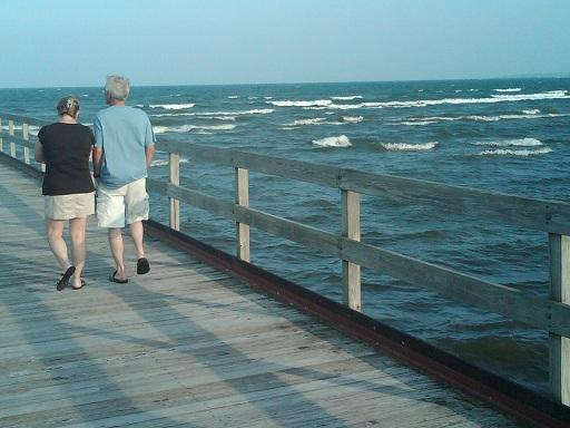 A couple goes for a walk on a pier over Lake Huron in Alpena, Michigan