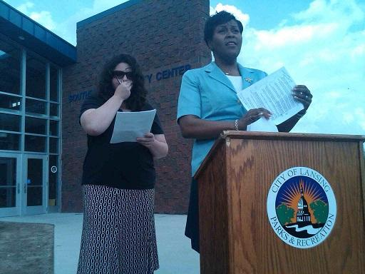 Lansing city council president A'Lynne Robinson (right) talks to the news media about the city's budget crisis, while council vice president Kathie Dunbar listens, outside the Southside Community Center