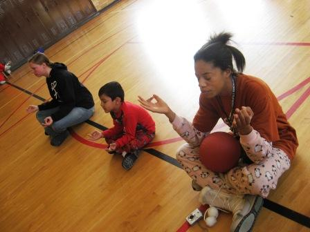 A student (center) at Bennett Elementary in southwest Detroit leads a brief meditation before getting to the games. Playworks Coach Sharon Brooks is to his right. Playworks Program Manager Lily Kreimer is left.
