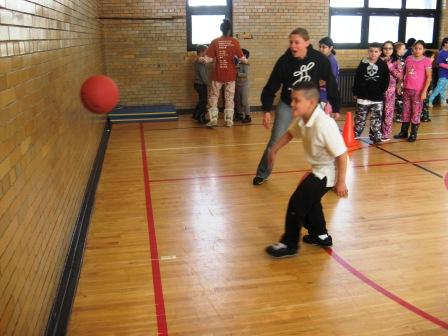 Playworks Program Manager Lily Kreimer encourages a Bennett Elementary student during a game of wall ball.
