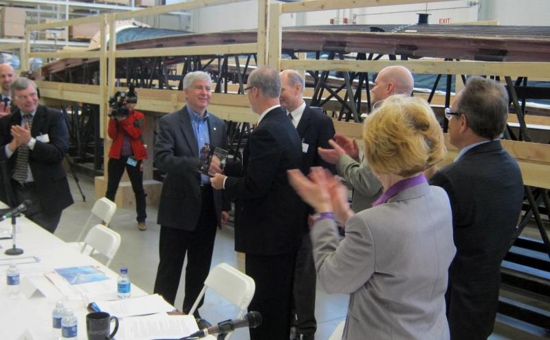 "Governor Snyder hands memebers of the Slikkers family his first ever ""Reinventing Michigan"" award Wednesday. The Slikkers own Energetx Composites, a spin-off of Tiara Yachts."
