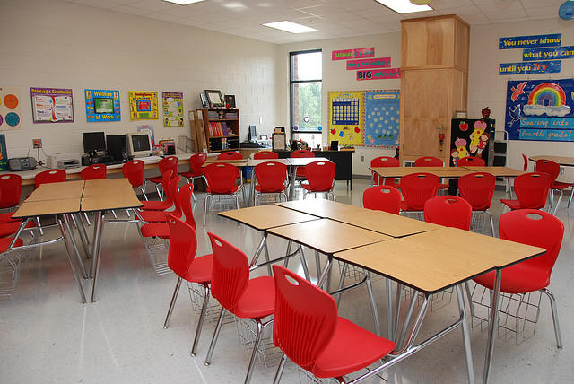 A long table surrounded by red chairs in a school classroom.