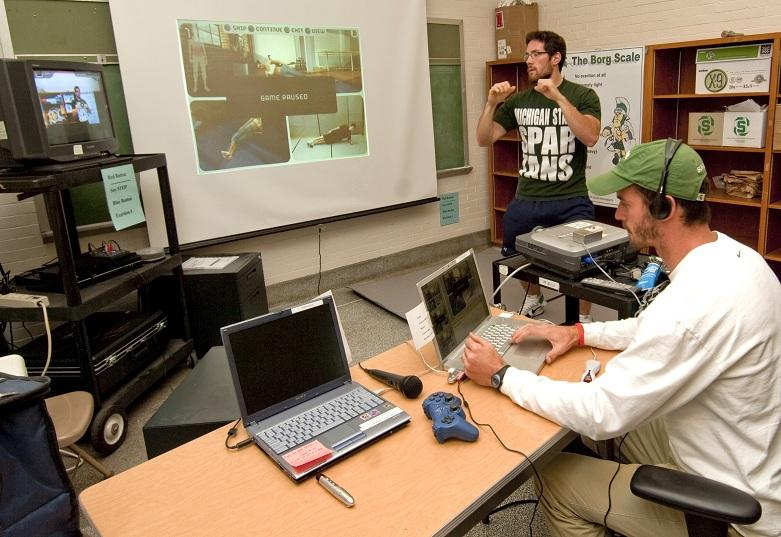Brandon Irwin (sitting) of the Department of Kinesiology conducts exercises with test subject Nik Skogsberg in the Health Games Lab. The technology was used to study motivational gains for people exercising with virtual workout partners. Photo by Derrick