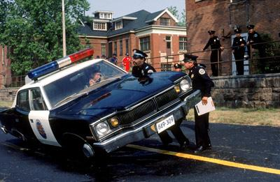 Lt. Moses Hightower (played by B. Smith) in the movie Police Academy, lifting a car
