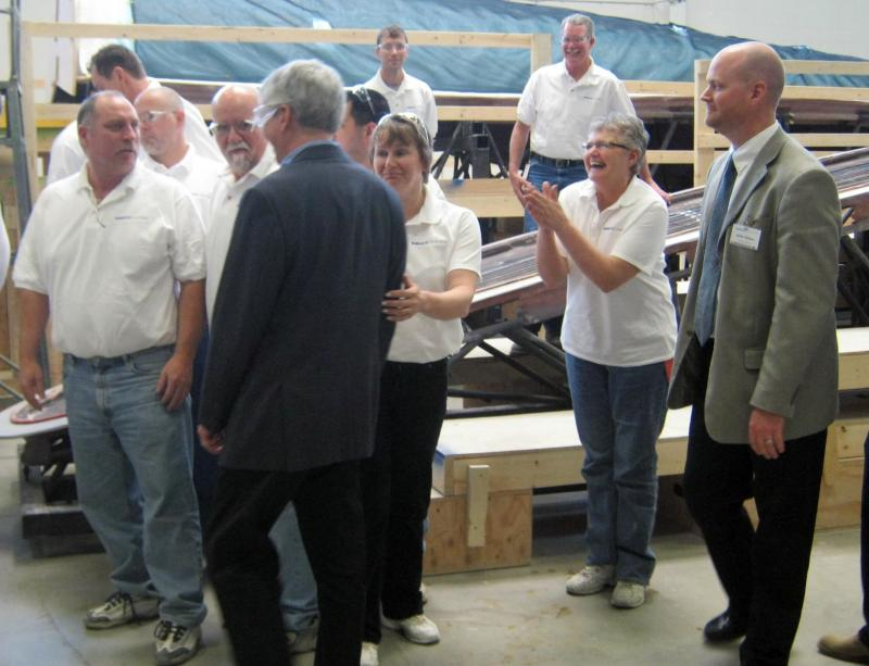 Governor Rick Snyder gave Energetx his first 'Reinventing Michigan' award in May 2011. Kelly Slikkers is at the far right. Nancy Jones laughs with Snyder while they prepare for a photo op in front of the blade.