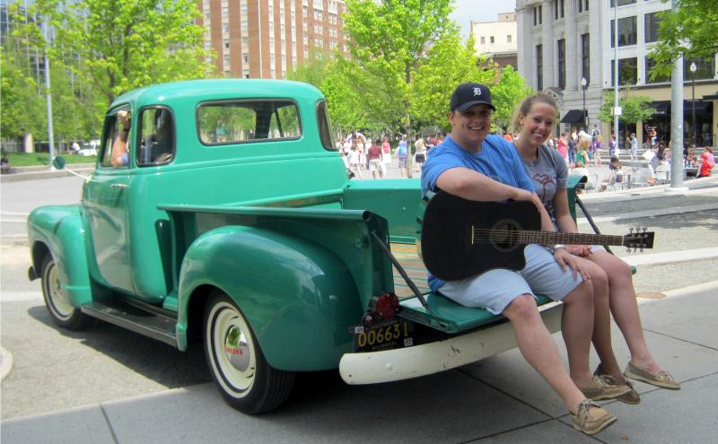 "Ryan Slusarzyk and Abbey Sloan sit in the back of a classic Chevy truck near Rosa Parks Circle. They have a line in the Grand Rapids lip dub ""drove my chevy to the levee,
