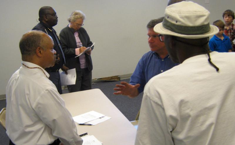 Benton Harbor's Emergency Manager Joe Harris (left) speaks with residents one-on-one following the public hearing on his budget Wednesday night.