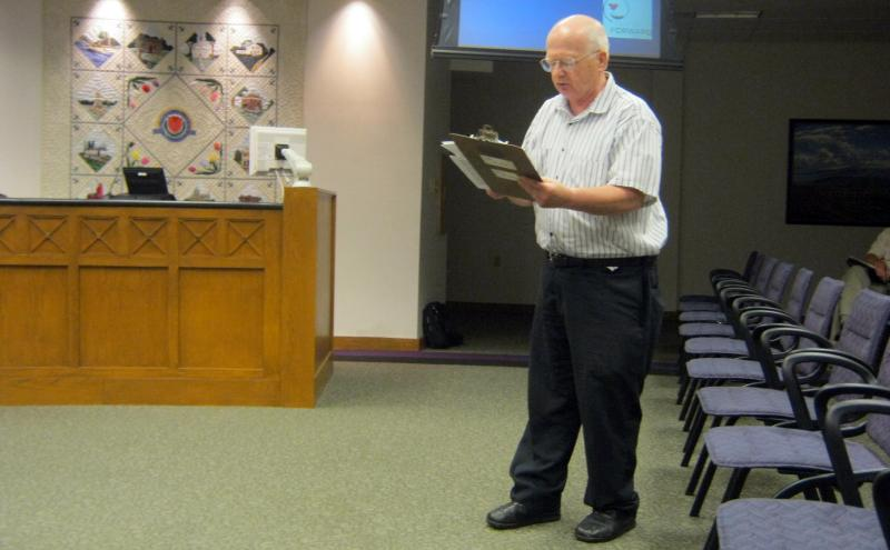 Reverend Ralph Houston reads Bible passages from a handout he gave Holland City Council members at a meeting in early June 2011.