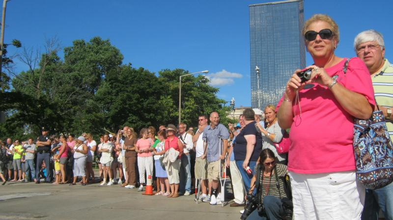 People watch and wait for the precession to head down Pearl Street to the Gerald R. Ford Museum.