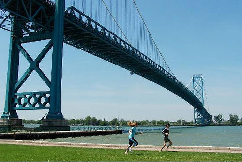 Joggers run under the Ambassador Bridge, which connects Detroit to Windsor, Ontario. Governor Snyder is pushing for another bridge across the Detroit River to be built.
