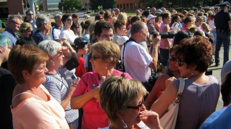The crowd of more than 1,000 people anxiously await the precession Thrusday afternoon.