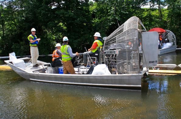 Crews working to clean up oil on the Kalamazoo River. They use airboats because they have less impact on the river.