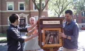 Chicago Awesome Foundation chapter members Drew Bradford (left) and Matt Dorn (right) help the Little Free Library's Rich Brooks put the first library up.