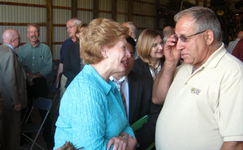 Senator Debbie Stabenow (D-MI) speaks with Jim May inside his barn in Sparta Monday afternoon.