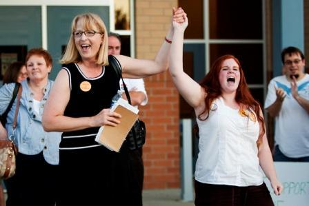 Central Michigan University Faculty Association President Laura Frey (left) cheers with Waterford Graduate Assistant Michelle Campbell, Sunday evening outside of Mount Pleasant High School.