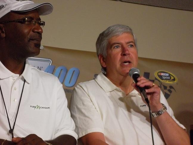 MEDC President Michael Finney (left) listens as Michigan Gov. Rick Snyder talks to reporters at the Michigan International Speedway prior to the start of the Pure Michigan 400