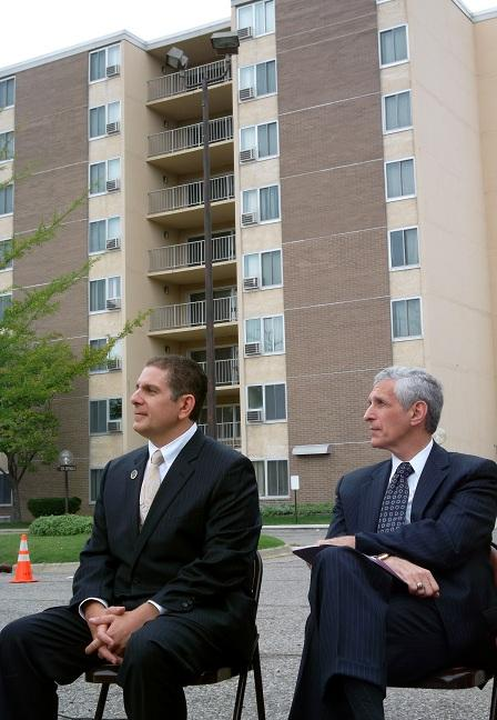Lansing mayor Virg Bernero (left) sits with Davenport University president Richard Pappas at a news conference discussing the proposed land swap.  The Oliver Towers stands in the background.