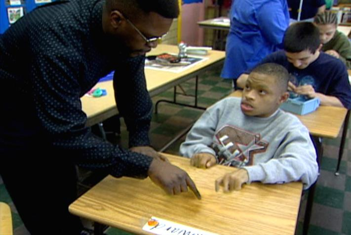 "Teacher Assistant Preston Taylor assists student with class assignment at Kettering West Wing, Detroit Public Schools. Kettering West Wing ranked at the top of the ""Top to Bottom"" list."